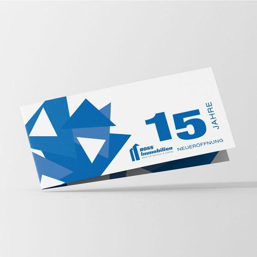 Boss Immobilien Einladungsfolder mit grafischen blauen Elementen links und Schrift rechts, 15 Jahre Neueröffnung