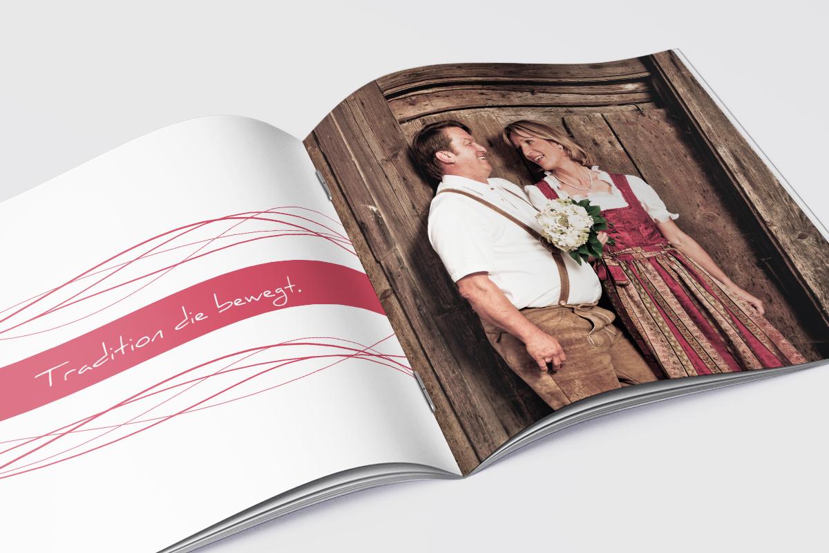 aufgeschlagene Broschüre, rechts Bild von Mann und Frau zusammen vor Holztür, links grafische Elemente und Schrift