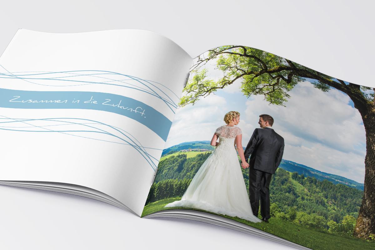 aufgeschlagene Broschüre, rechts Bild von Mann und Frau auf Wiese Hand in Hand, links grafische Elemente und Schrift