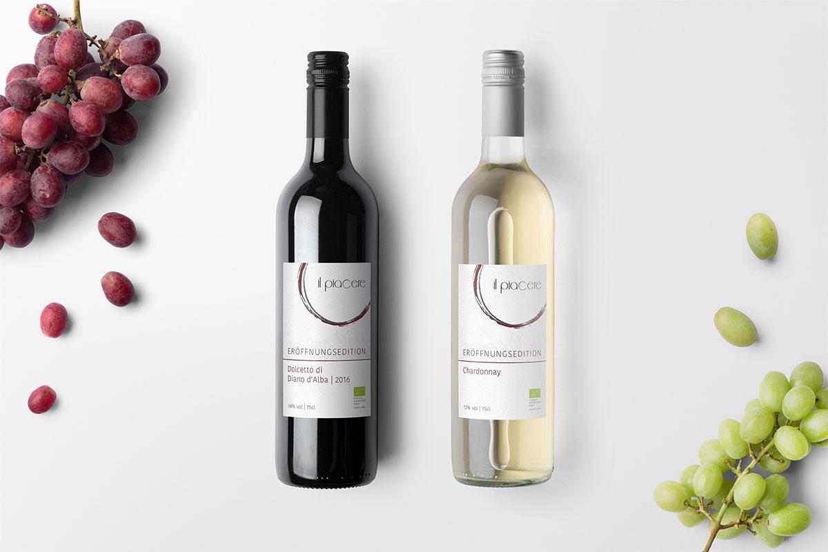 Design Rotwein- und Weißweinflasche nebeneinander auf hellem Hintergrund, linkr und rechts im Bild Weintrauben