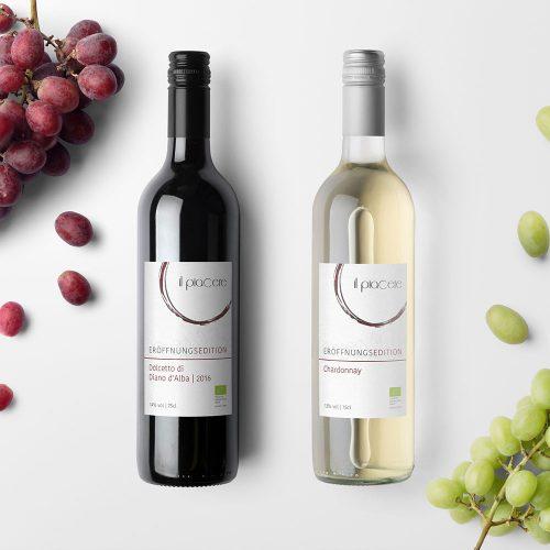 Design Wein, Rotwein- und Weißweinflasche) nebeneinander auf hellem Hintergrund, links und rechts im Bild Weintrauben